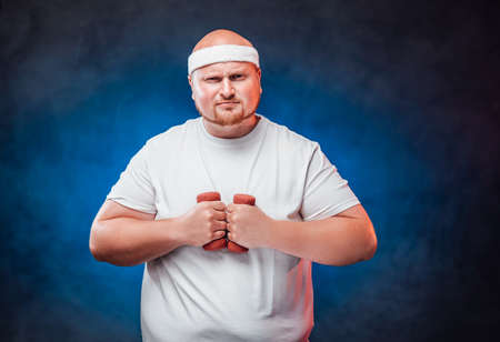 Tubby man in a white tracksuit holds dumbbells in his hands and very tensely looks directly at the camera