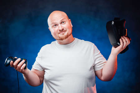 Very fat gamer in a white t-shirt holds a joystick and vr glasses in his hands, looking at the camera very seriously
