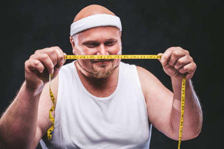 Happy plump man in a white t-shirt looks at a measuring tape in his hands with a big smile