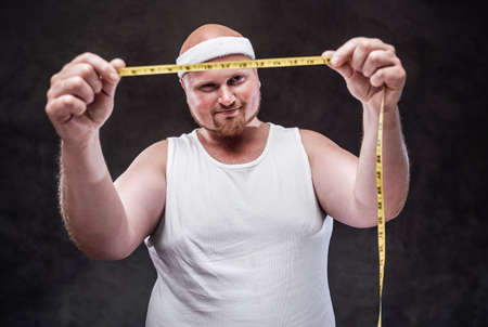 A bald plump man in a white t-shirt looks at a measuring tape in his hands with a big smile