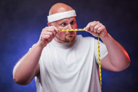 A plump man with a shocked face, dressed in a white t-shirt looks at the yellow measuring tape in his hands