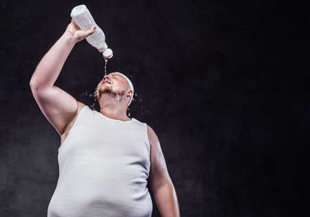 Chubby bald man, after working out, pours cold water from a bottle on his face