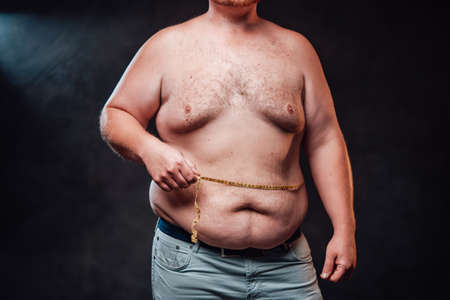 Chunky man is measuring his fat belly with a yellow measuring tape, standing on the black backgrund 免版税图像