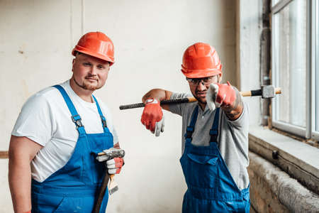 Funny workers discussing the upcoming work, looking at the camera, holding a big sledgehammer