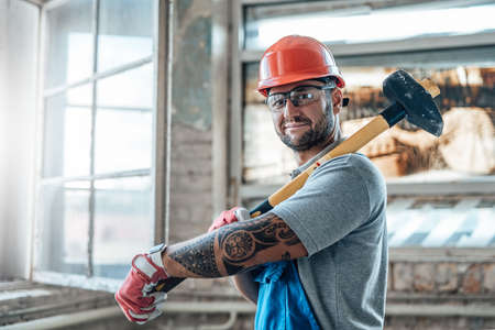 Smiling worker stands near the window at a construction site. He is wearing a red safety helmet and he holds a sledgehammer in his hands.