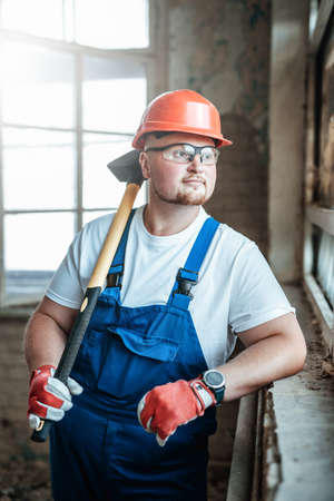 A tired worker stands near the window at a construction site. He is wearing a red safety helmet and he holds a sledgehammer for repairs in his hands.