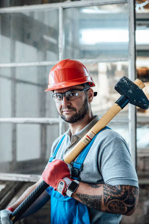Attractive constructional worker with tattos stands near the window at a construction site. He is wearing a red safety helmet and he holds a sledgehammer for repairs in his hands.