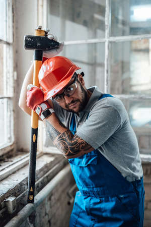 Worker, taking a short break, stands near the window at a construction site. He is wearing a red safety helmet and he holds a sledgehammer in his hands.