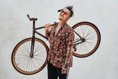 Very expressive and stylish guy in sunglasses and hawaiian shirt holding the bike on his shoulder. Studio shot on a white wall