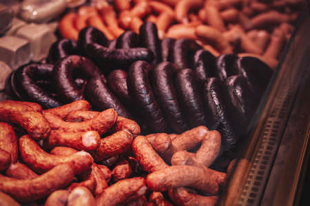 Cold and fresh smoked meat in the market. Butcher shops meat counter. Saling sausages and hum.