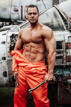 Escaped prisoner prepares to repair old crashed airplane. Muscular guy in technician prisoners fashion.