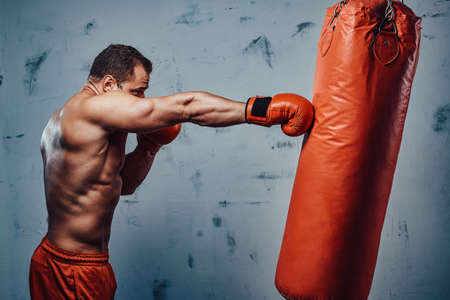 Graceful sportsman with strong hands and red gloves punching hanging bag in gym.