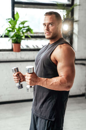 Powerful guy with muscular hands and huge biceps posing with dumbells in vintage studio room with special illumination.