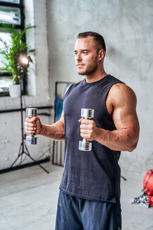Muscular guy in black shirt holding and practicing with dumbells in custom gym with plants and spotlights. Banco de Imagens