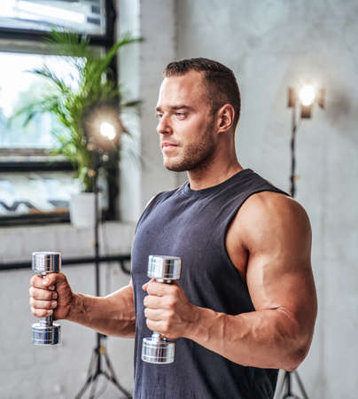 Seductive and muscular guy in shirt and strong hands posing with dumbells in custom sport room with plants and spotlights.