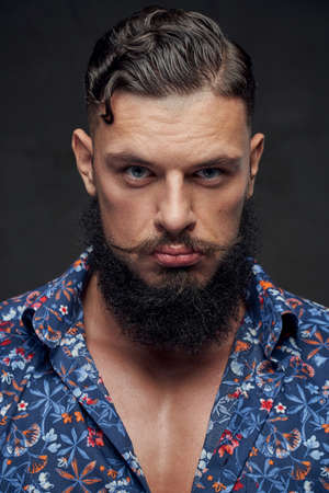 Masculine and stylish guy with fashionable haircut and beard posing in shirt in gray background. Stock Photo