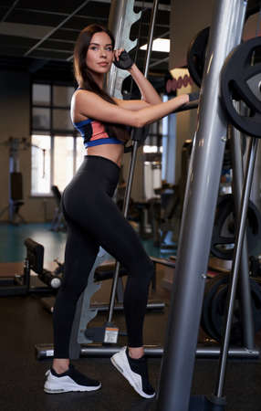 Pretty and sportive brunette with slim figure in sportswear posing with hand on barbell in modern gym.