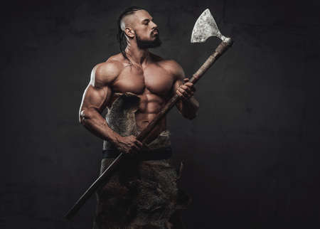 Nord muscular fighter with dreadlocks and beard posing looking at his axe which he holding on hands in dark background.