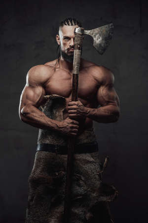 Ancient muscular viking staying with naked torso and dreadlocks holding his axe hiding half of his face in dark background. Reklamní fotografie