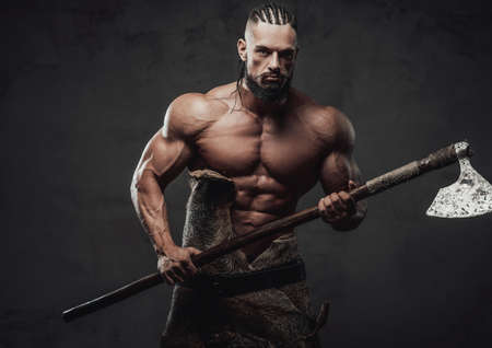 Brutal bodybuilder in fashion of ancient furios viking posing with naked torso and dreadlock in dark dirty background.