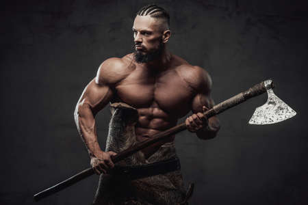 Furious and bearded viking warrior with naked torso and huge biceps prepared to fight holding his weapon in dark background.