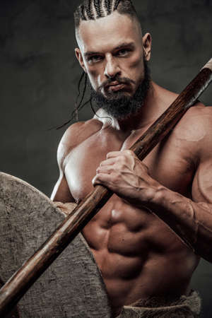 Close up photography of bearded and muscular viking with dreadlocks which holding shield and axe in dark background.