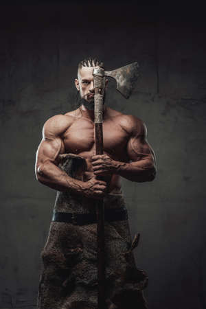 Brutal and powerful viking warrior with dreadlocks and beard posing with axe which covers half of his face in dark background. Reklamní fotografie