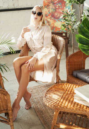 Graceful and glamour businesswoman with blond hairs in robe posing sitting on chair in luxurious hotel room with styled furniture.
