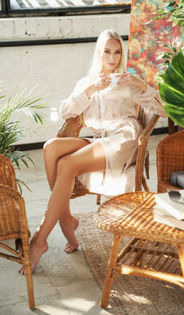 Beautiful and elegance madam with blond hairs in robe having a tea time sitting on chair in hotel room with styled design in sunrise.