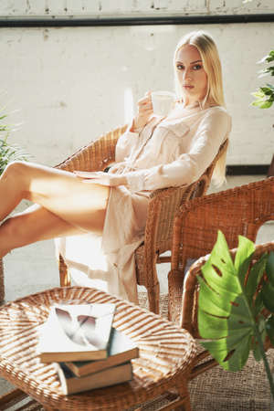 Elegance madam with blond hairs and legs in white robe posing on chair holding tea cup in her luxurious hotel room.