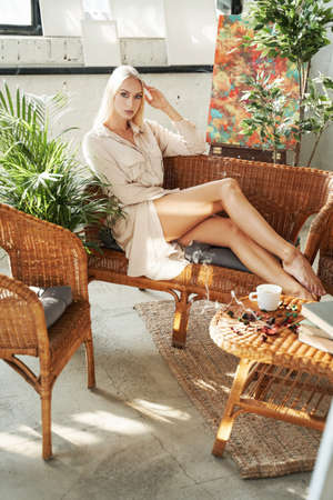 Attractive and elegance woman with blond hairs in white robe relaxing on sofa and posing lying down on sofa in luxurious hotel.