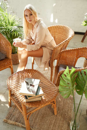 Graceful attractive girl in robe posing on chair holding tea cup around bamboo furniture in luxurious warm hotel room.