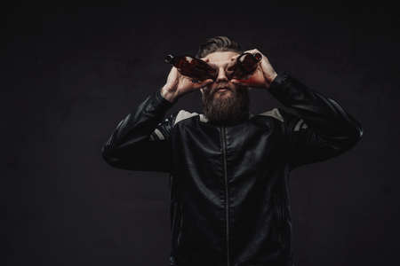 Haired brutal guy in black leather jacket in dark studio background holding empty bottles like binoculars and looking throught its.