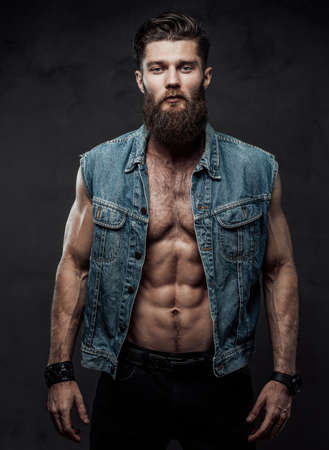 Brutal and handsome guy with torso beard and jewellery on his hands posing standing in dark background.