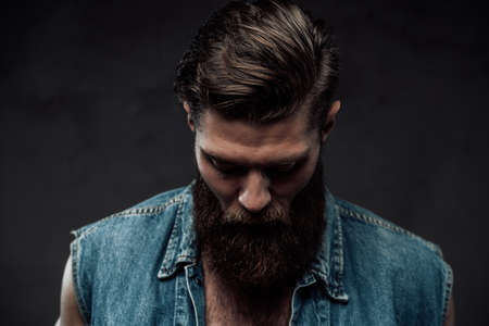Dressed in modern casual clothing brutal bearded guy with stylish haircut and brown hairs posing looking down in dark background.