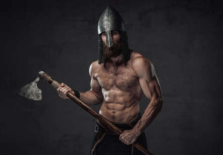 Nord barbarian with naked torso and beard in helmet posing holding his two handed axe in dark studio background. Reklamní fotografie