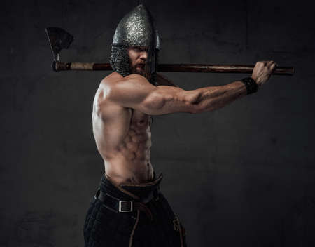 Furious and muscular northern marauder with naked torso and helmet posing calling to war holding his two handed axe. Stock fotó