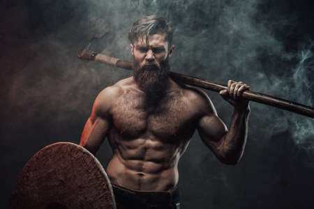Muscular and angry nord warrior posing in dark background with smoke holding shield and axe behind his back.