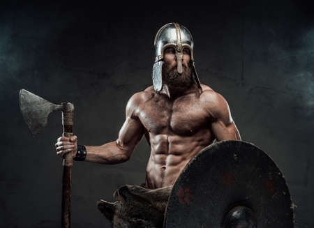Haired and muscular viking with beard and helmet on him posing holding his axe and shield in dark studio room with spotlight. Reklamní fotografie