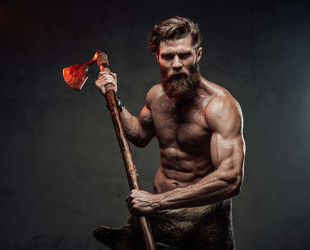 Shirtless medieval warlike viking with beard and muscular build posing holding two handed axe in dark studio background.