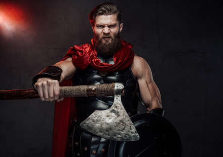 Warlike and aggressive roman fighter with beard and red cloak in dark armor posing with outstretched arm holding axe in dark background.