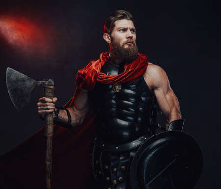 Muscular and warlike rome guardian with shield and axe in black armor and red mantle staying in dark room with spotlights.