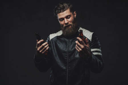 Filtered and atmosphetic photography of bearded and handsome guy with modern haircut in jacket which holding bottles in dark background. 免版税图像