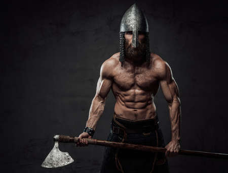 Nude and warlike viking marauder with beard and helmet posing holding his two handed axe in dark background.