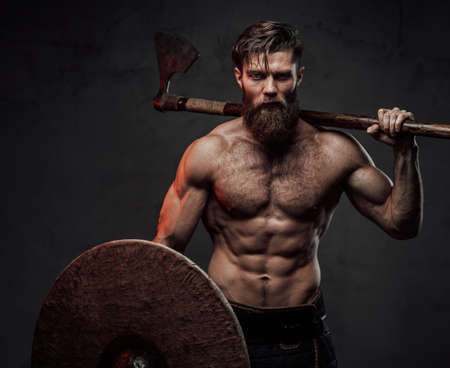 Warlike and furious viking with naked torso and beard staying in dark background holding shield and two handed axe behind his back. Stock fotó