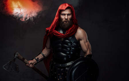 Military bearded roman in red hood and dark armor which holding an axe and shield posing in studio room with spotlight and smoke.
