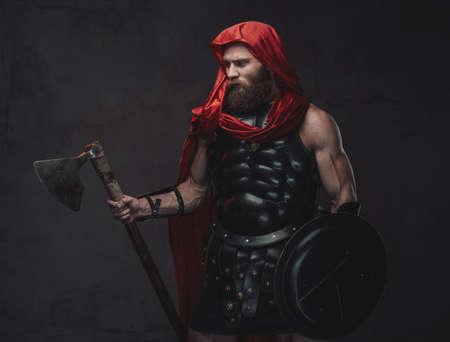 Dark and atmospheric studio room with spotlight and muscular bearded roman warrior with axe and shield in dark armor and cloak.