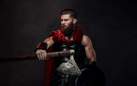 Handsome and bearded rome fighter in combat costume posing looking away and holding axe and shield in dark background. Banco de Imagens