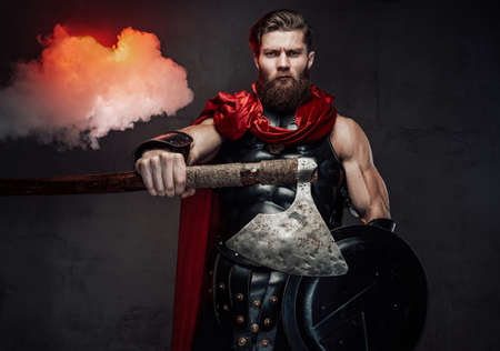 Violent and muscular rome guardian with beard and black armour putting his hand out holding an axe in dark background. Banco de Imagens