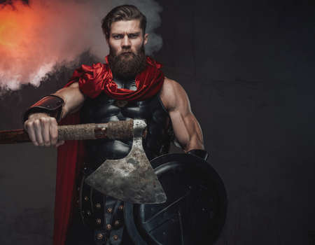 Combat male roman in dark armor with red cloak and beard posing putting his hand out which holding axe in atmospheric studio room.